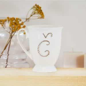 """Porcelianinis puodelis su """"Č"""" raide"""