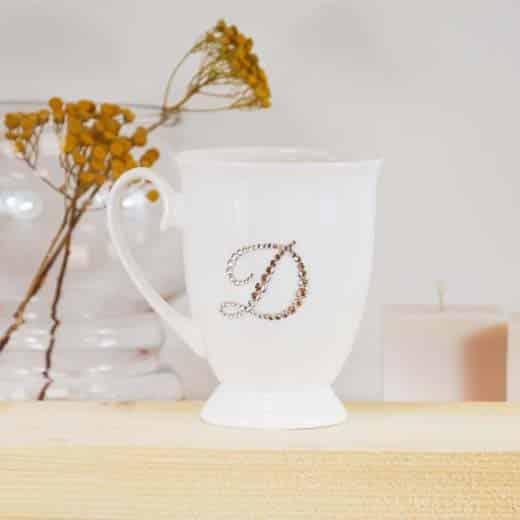 "Porcelianinis puodelis su ""D"" raide"