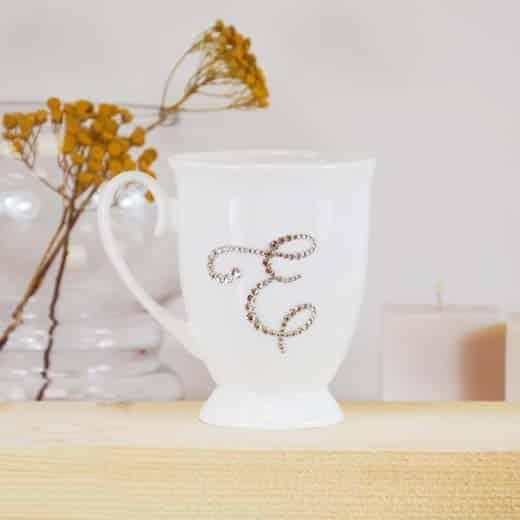 "Porcelianinis puodelis su ""E"" raide"