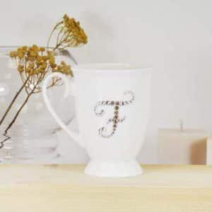 "Porcelianinis puodelis su ""F"" raide"