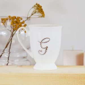 """Porcelianinis puodelis su """"G"""" raide"""