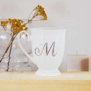 """Porcelianinis puodelis su """"M"""" raide"""