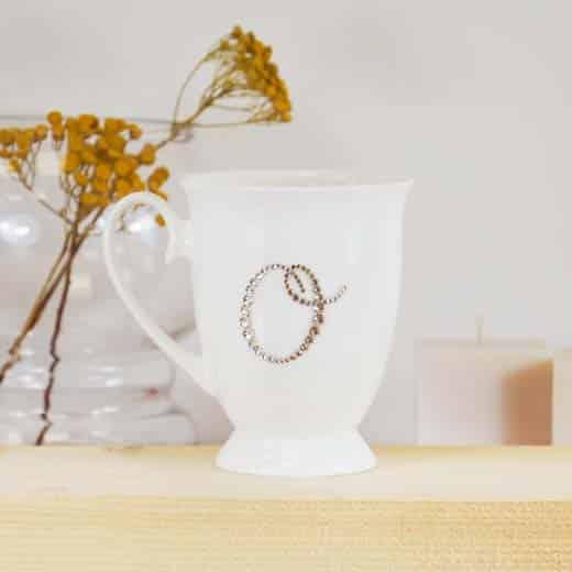 "Porcelianinis puodelis su ""O"" raide"