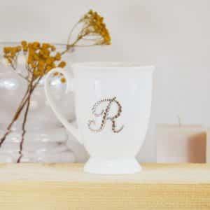 """Porcelianinis puodelis su """"R"""" raide"""