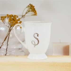 """Porcelianinis puodelis su """"S"""" raide"""