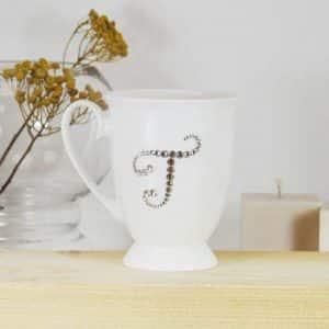 "Porcelianinis puodelis su ""T"" raide"