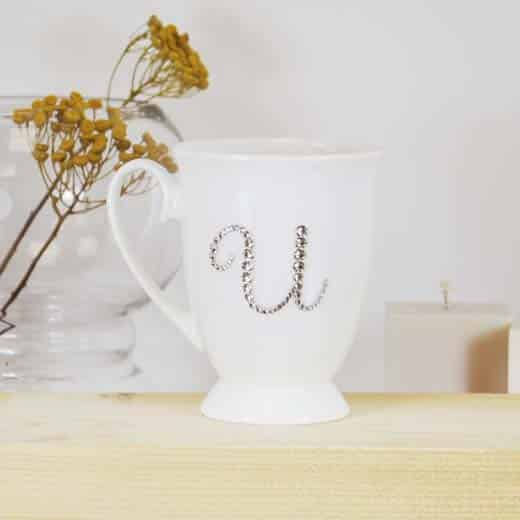 "Porcelianinis puodelis su ""U"" raide"