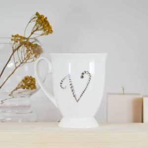 "Porcelianinis puodelis su ""V"" raide"